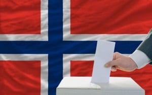 Stemmeurne med norsk flagg i bakgrunnen