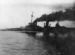 Den stolte tyske slagkrysseren SMS Seydlitz er på vei hjem etter slaget ved Jylland juni 1916. Hun er sterkt skadet og man kan se at skipet er på nippet til å kapseise etter en torpedo som nesten senket henne. Foto: Wikimedia Commons.