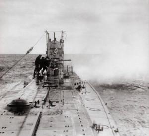 Mannskapet på en tysk ubåt avfyrer dekkskanonen mot et ukjent mål. Ubåtene hadde et begrenset antall torpedoer med seg og det var langt billigere og langt mer treffsikkert å benytte dekkskanonen mot fiendtlige mål. Før vestmaktene begynte å sende væpnet eskortes med skipene som gikk over Atlanteren hadde ubåtenes kapteiner tid til å varsle fraktskip om at de ville senke dem slik at mannskapet rakk å gå i livbåtene, men etter hvert som krigen gikk ble tyskerne tvunget til å gå til uinnskrenket ubåtkrig, uten hensyn til nøytrale skip eller sivile skip og liv.