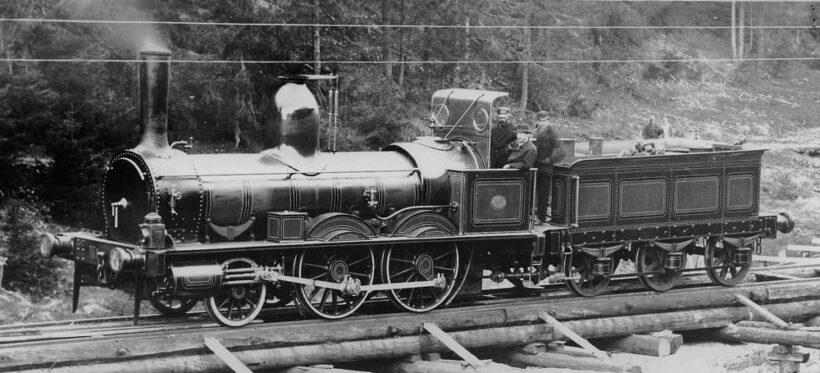 Et av de første Stephenson-lokomotivene på Norges hovedjernbane mellom Bøn og Eidsvoll i 1860. Jernbanen var både en transportrevolusjon først for trelastnæringen og etter hvert som persontransport, samt en viktig arbeidsplass for tusenvis av nordmenn på 1800-tallet, særlig i nedgangstider. Bilde: Wikimedia Commons
