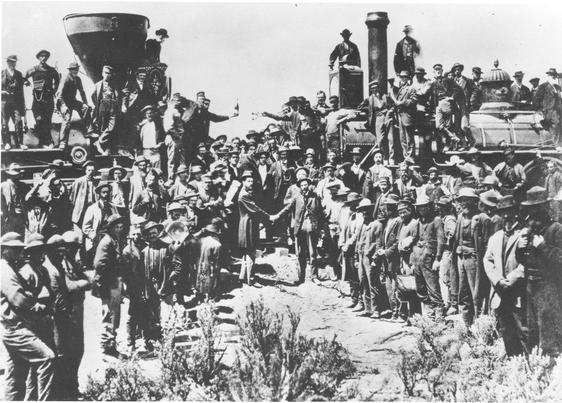 Seremonien hvor den siste spikeren ble drevet ned i jernbanesvillene som endelig forbandt den amerikanske østkysten med vestkysten i delstaten Utah 10. Mai 1869. Representanter for de to selskapene som hadde startet i hver sin ende av kontinentet, Central Pacific og Union Pacific Railroad, håndhilser blant dusinvis av hardbarkede arbeidere.