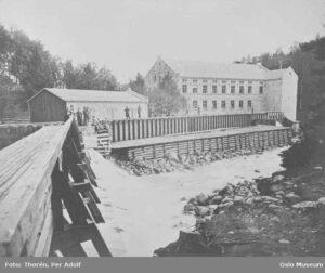 """Bilde av det nedre spinneriet ved Nydalens Compagnie langs Akerselva tatt en gang mellom 1874 og 1878. Spinneriet ble etablert i 1945 under navnet """"Nydalens Bomuldsspinderi"""" av Adam Hiorth. Kilde: Oslo Museum - Byhistorisk samling, Creative Commons 3.0-lisens."""