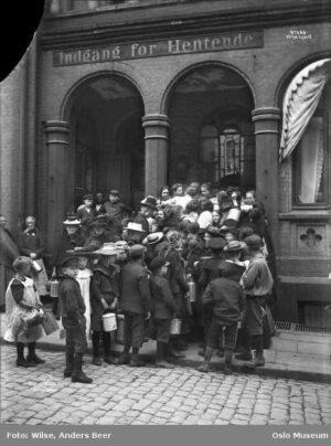 Barn står i matkø utenfor Christiania Dampkjøkken i 1903. Bilde: Oslo Museum - Byhistorisk samling. Creative Commons 3.0-lisens