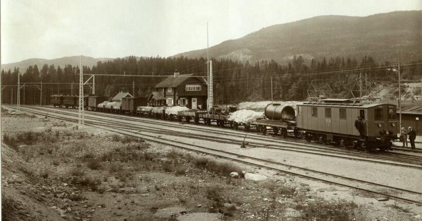 Rjukanbanen ble bygget i forbindelse med Norsk Hydros utbygging på Rjukan og ble i 1911 landets første elektriske jernbane. Bildet viser et e-lokomotiv ved TInoset stasjon i 1911. Foto: Nasjonalbiblioteket, ingen kjent opphavsrett