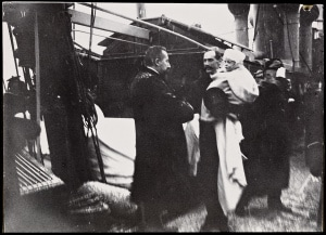 """Statsminister Christian Michelsen mottar kong Haakon 7 og kronprins Olav ombord det norske marinefartøyet """"Heimdal"""" i Kristiania, 25. november 1905. Fotograf: Jens Hilfling-Rasmussen, kilde: Nasjonalbiblioteket. Ingen kjent opphavsrett."""